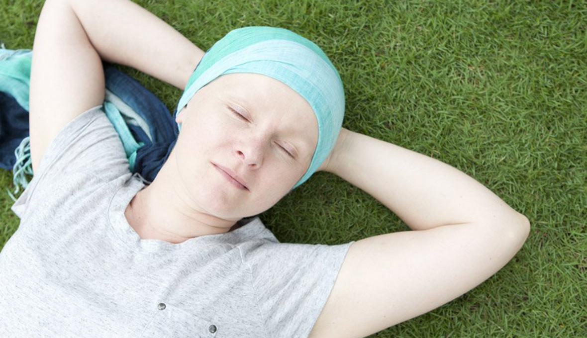Young woman with head scarf lying in the grass